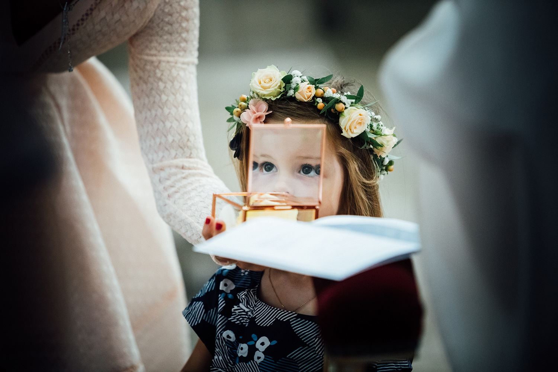 Petite fille regarde à travers une boite en verre les alliances. Quand la petite fille apporte les alliances, son regard à travers la boite à bijoux. Photo réalisée pour le mariage de Laure & Jean-Baptiste à Epernay.