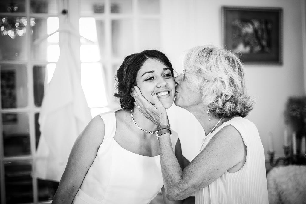 Une maman embrasse sa fille sur la joue, la robe de mariée est accrochée derrière elles. L'amour d'une mère pour sa fille à quelques heures de son mariage.